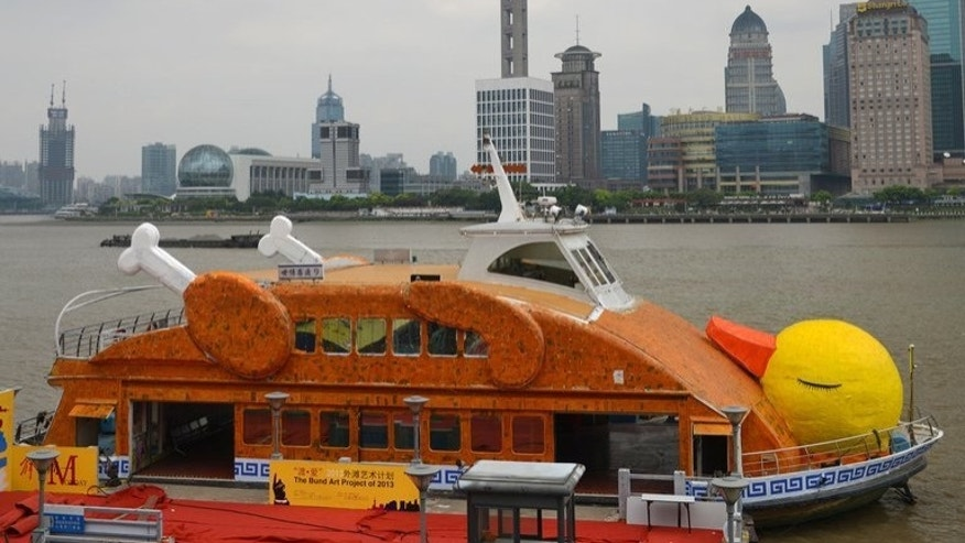 A boat made to look like a roasted duck is seen on the Huangpu River in Shanghai on August 27, 2013. A well-known restaurant, Quanjude, sought to take advantage of the Rubber Duck installation by using it to advertise its own showpiece, Peking duck.