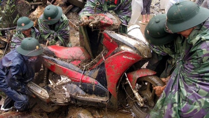 This photo, taken by the Vietnam News Agency on September 5, 2013, shows soldiers pulling out a motorcycle from debris at the scene of flash floods in Sapa district, northern province of Lao Cai. At least 21 people have been killed as flash floods and landslides ravaged mountainous areas in northern Vietnam.
