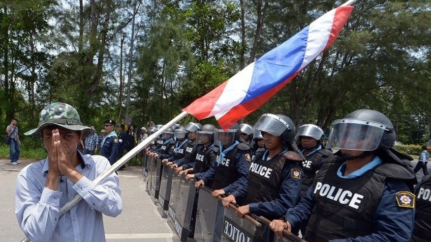 A rubber farmer gives a traditional greeting to the riot police during a protest near an airport in Surat Thani province, on September 4, 2013. In recent days angry rubber farmers have blocked roads, train lines and even -- briefly -- the entrance to an airport in Thailand's south where plunging global prices for the commodity have hit the local economy hard.