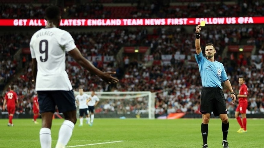 Referee Ivan Kruzliak books England's Daniel Welbeck (L) during the World Cup 2014 Group H qualifying match against Moldova at Wembley Stadium in north London on September 6, 2013. Roy Hodgson admitted he had a dilemma on his hands after the England manager's attacking selection crisis deepened following the 4-0 win over Moldova