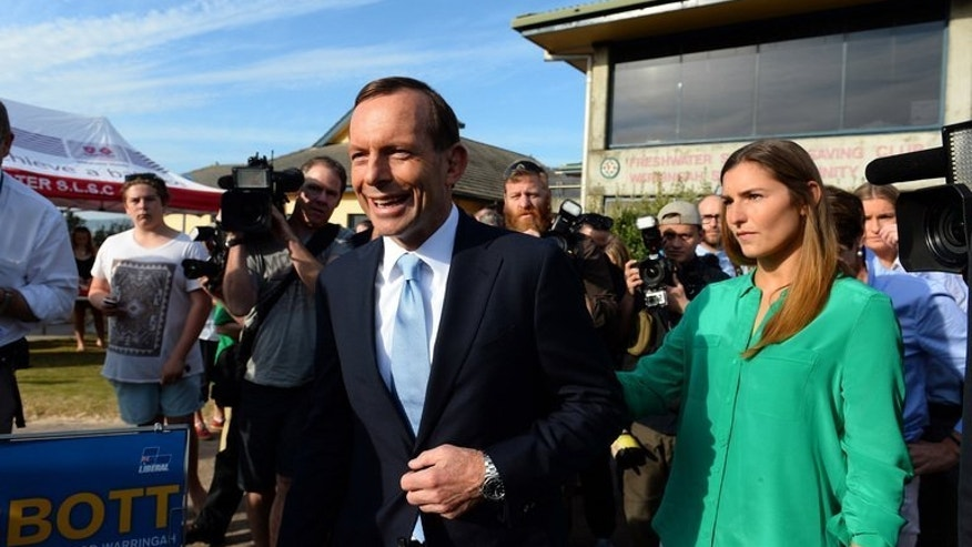 Australian opposition leader Tony Abbott (C) outside a polling station in Sydney on September 7, 2013. The conservative challenger was heading for a major victory over Labor Prime Minister Kevin Rudd on Saturday as millions of Australians voted in national elections.