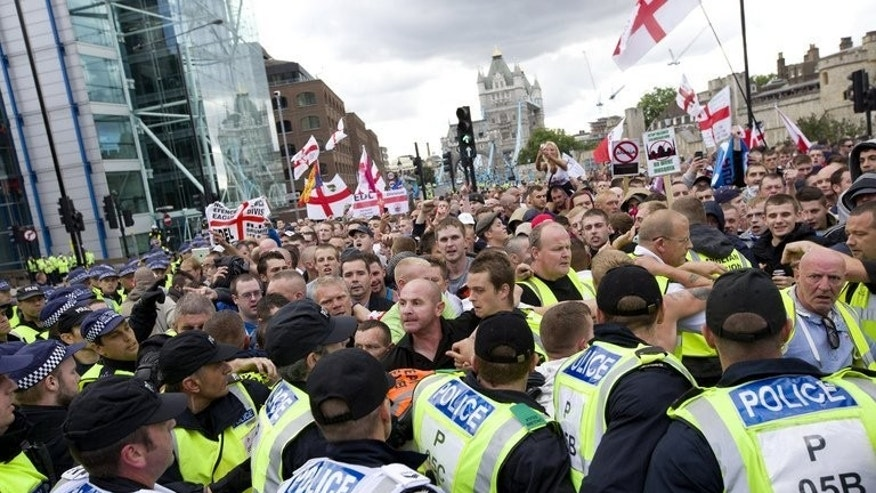 Members of the right-wing English Defence League (EDL) are contained behind a line of police as they march across Tower Bridge in London on September 7, 2013.