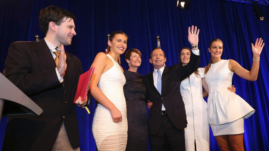 Sept. 7, 2013: A man, left, intrudes as Tony Abbott, third right, and his daughters Frances, second left, Louise, second right, and Bridget, far right, and his wife Margaret, third left, come to the stage to celebrate Tony's election victory in Sydney following his win in Australia's national election.