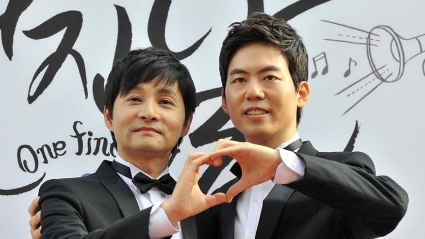 "South Korean movie director Kim Jho Gwang-Soo (left) embraces his partner Kim Seung-Hwan during a press conference before their wedding in Seoul, on September 7, 2013. Kim Jho Gwang-Soo -- a prominent gay rights campaigner has ""married"" his partner in South Korea, where same-sex marriage is not legally recognised."