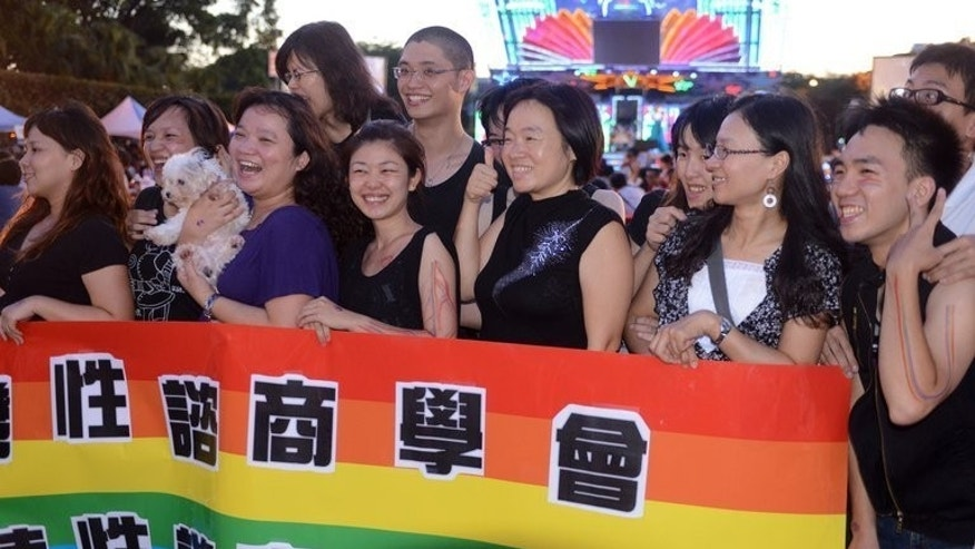 "Local residents stand behind a rainbow banner during a same sex dinner party in front of the Presidential Office in Taipei on September 7, 2013. More than 1,200 Taiwanese people joined a mock ""wedding banquet"" aiming to drum up support for same-sex marriage bill due to be sent to parliament soon, organisers said."