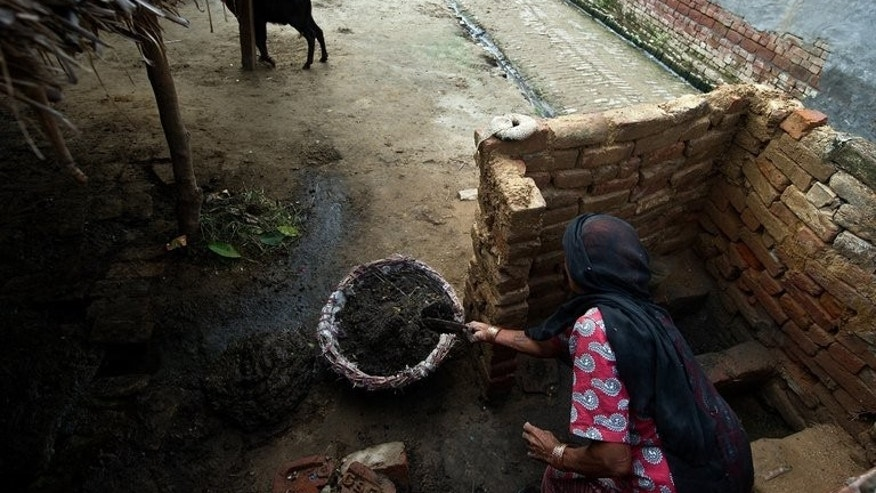"An elderly manual scavenger collects human waste while cleaning a toilet in Nekpur village, Uttar Pradesh, on August 10, 2012. Indian lawmakers have passed a long-awaited bill to ban manual scavenging -- the clearing of human waste from toilets -- by workers seen as the ""ultimate untouchables"" under the country's ancient Hindu caste-hierarchy."