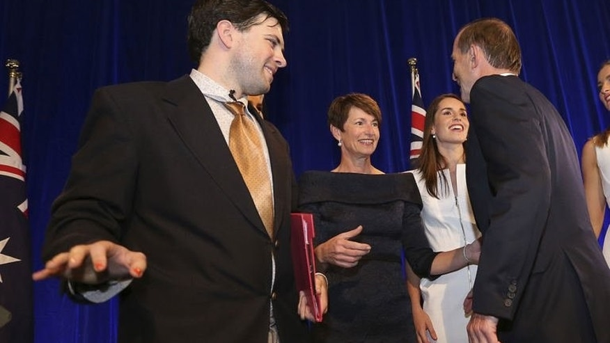 Stage-crasher 'Twiggy Palmcock' stands next to new Australian PM Tony Abbott and his family on September 7, 2013. He managed to shake Abbott's hand and pat the arm of his daughter before being escorted off the stage by security guards.