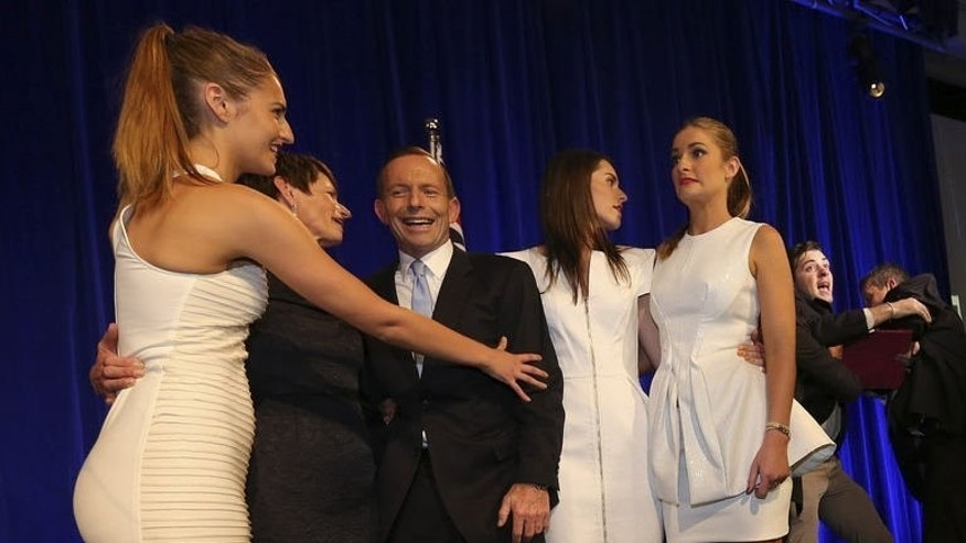 Security guards remove an intruder from the stage after he shook Tony Abbott's hand on election night, September 7, 2013. The Business Insider website named the stage-crasher as 25-year-old Fregmonto Stokes.