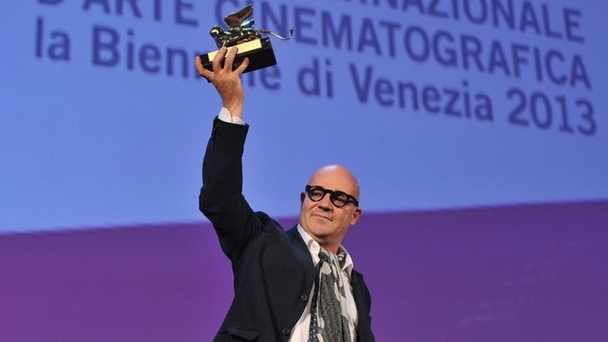 """Italian director Gianfranco Rosi poses with the Golden Lion for Best Film he received for his movie """"Sacro GRA"""" during the award ceremony of the 70th Venice Film Festival on September 7, 2013 at Venice Lido."""