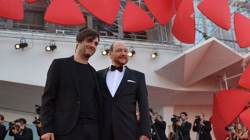 """Director Alexandros Avranas (L) and actor Themis Panou pose on the red carpet as they arrive for the award ceremony of the 70th Venice Film Festival on September 7, 2013 at Venice Lido. The best actor prize went to Panou for his role as father to a family which harbours a deep secret in Avranas's """"Miss Violence""""."""