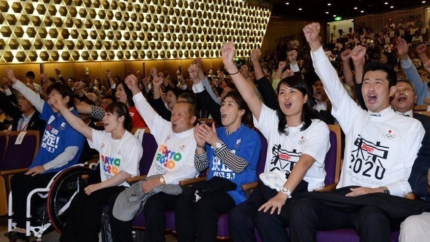 L-R: Japanese paralympian Wakako Tsuchida, Japanese Olympians, Hiromi Miyake, her father Yoshiyuki Miyake, Saori Yoshida, Ai Shibata and Junichi Miyashita clinch their fists in jubilation after Tokyo was named for the 2020 Olympic bid in Buenos Aires during the live streaming event in Tokyo on September 8, 2013.