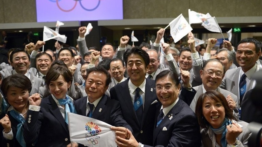 Japanese Prime Minister Shinzo Abe (C) celebrates alongside Tokyo 2020 delegation members after IOC president Jacques Rogge announced the Japanese capital to be the winner of the bid to host the 2020 Summer Olympic Games, during the 125th session of the International Olympic Committee (IOC), in Buenos Aires, on September 7, 2013.