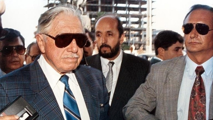 Chile's former dictator Augusto Pinochet (L) arrives at a hotel in Montevideo on February 24, 1993. Forty years after the military coup instigated by Pinochet, his legacy is being questioned.