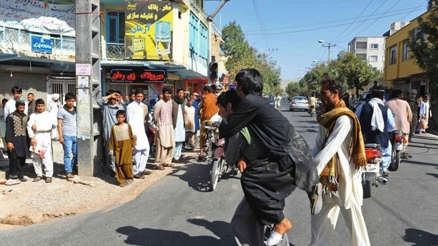 A demonstrator is carried after getting injured during a demonstration outside the Iranian consulate in Herat on September 7, 2013. At least one person was killed and 4 wounded when demonstrators tried to storm the Iranian consulate in Western Afghanistan to protest not extending their visas, officials said.