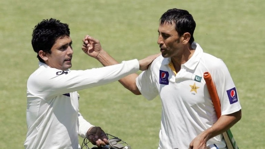 Pakistan batsman Younis Khan (right) is congratulated by Adnan Akmal (left) during the fourth day of the first cricket Test against Zimbabwe in Harare on September 6, 2013. Pakistan beat Zimbabwe by 221 runs on the fifth day.