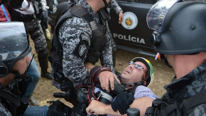 Riot police aid an injured photographer during clashes with protestors in Brasilia on September 7, 2013.