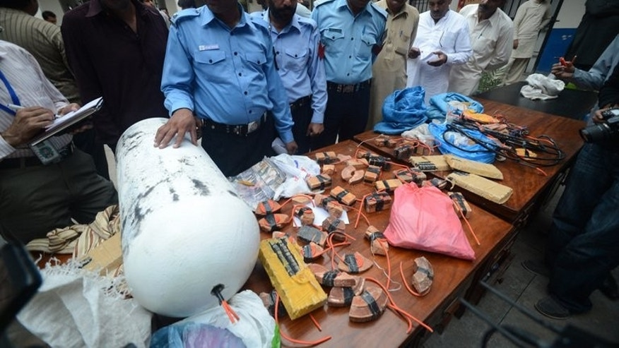 Policemen show seized explosive material in Bhara Kahu, on the northeastern outskirts of Islamabad, on August 31, 2013. During Zardari's presidency religious violence has spiralled and a surge in terrorist attacks means shootings and bombings are now a daily reality.