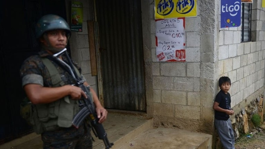 A child looks at a soldier standing guard at a crime scene where eleven people were killed by alleged members of a gang in San Jose Nacauil municipality, 20 km north of Guatemala City, on September 8, 2013.