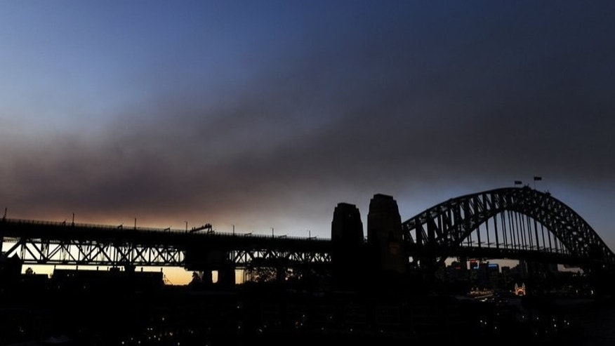 "A smoke haze creates an unusual sunset over the Sydney Harbour Bridge, on May 11, 2010. New premier Tony Abbott has proposed a so-called ""Direct Action"" plan to tackle pollution in Australia -- among the world's worst per capita emitters due to its dependence on coal-fired power stations and mining industry."