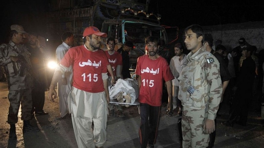 Pakistani rescuers shift a dead body on a stretcher at the bomb blast site in Quetta on September 8, 2013.