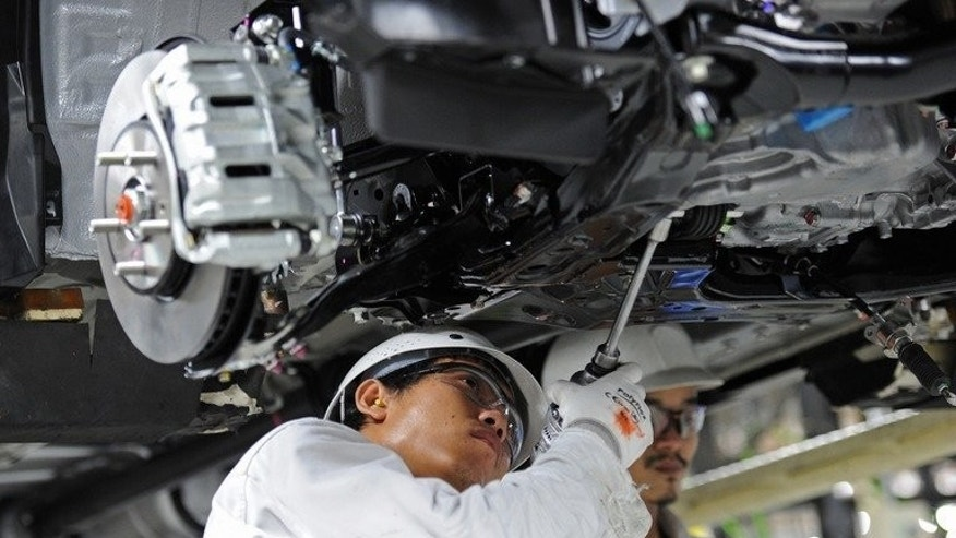 This picture taken on June 18, 2013 shows employees working on a car assembly line at a Honda plant in Ayuthaya, north of Bangkok.