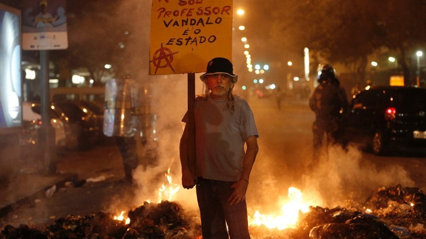 "A man holds a sign that reads in Portuguese ""Respect, I'm a teacher, the vandal is the state"" at a burning barricade set up by protesters in Rio de Janeiro, Brazil, Saturday, Sept. 7, 2013. Police used tear gas and rubber bullets to scatter anti-government protesters who interrupted an independence day military parade in Rio de Janeiro, and demonstrations in dozens of other cities led to some scuffles between marchers and police. (AP Photo/Silvia Izquierdo)"