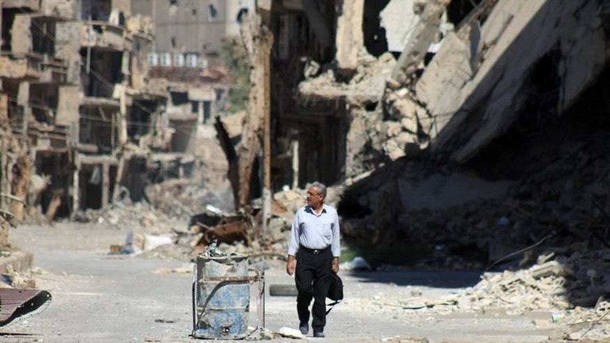 A Syrian man walks down a destroyed street in the centre of Deir Ezzor, the largest city in eastern Syria, on September 6, 2013. British Foreign Secretary William Hague has called for a strong response to the use of chemical weapons in Syria, saying the issue went wider than the conflict in the Middle Eastern country.