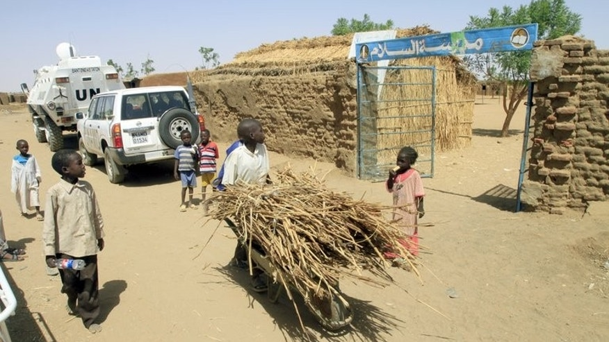 A child pushing a wheelbarrow walks past the entrance to a school in the North Darfur state capital of el-Fasher, on June 17, 2013. Two Red Cross drivers held for almost two weeks in Sudan's troubled Darfur region have been safely released, their organisation said.