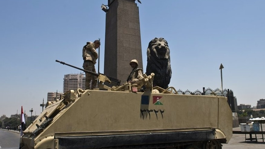 Egyptian soldiers stand guard on top of their armoured personnel carrier near Cairo's Tahrir square on July 26, 2013. The deadly crackdown on Islamists across Egypt could radicalise their ranks and at the same time further bolster the powerful army during the country's transitional phase, experts say.