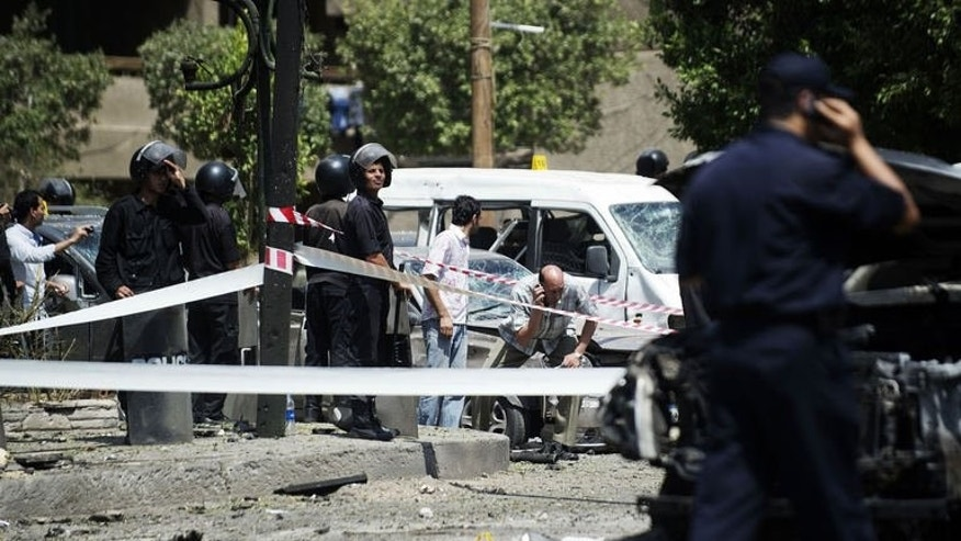 Security forces inspect the scene of a bomb that targeted the convoy of Egyptian Interior Minister Mohammed Ibrahim in Cairo on September 5, 2013.