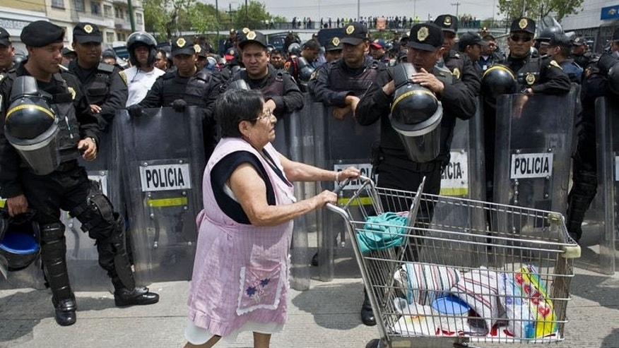 A woman selling food walks past police standing guard as teachers protest against an education reform in Mexico City, on September 5, 2013.