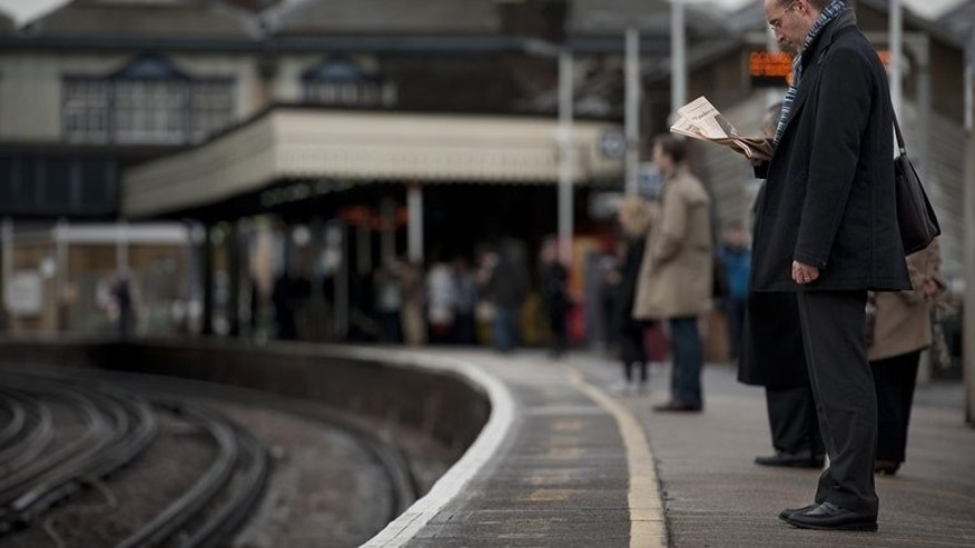 """Passengers wait for a train at Clapham Junction station in London in 2012. A public spending watchdog on Monday said the Department of Transport had failed to present a """"convincing strategic case"""" for the controversial ??50 billion HS2 high-speed rail project."""