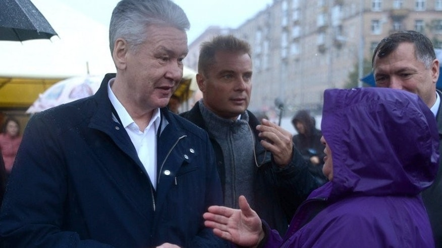 Sergei Sobyanin speaks with a local resident in Moscow on September 6, 2013. Kremlin-backed Sobyanin is expected to win the Sunday poll with a majority, while Alexei Navalny is set to come second with around 20%, according to opinion polls.