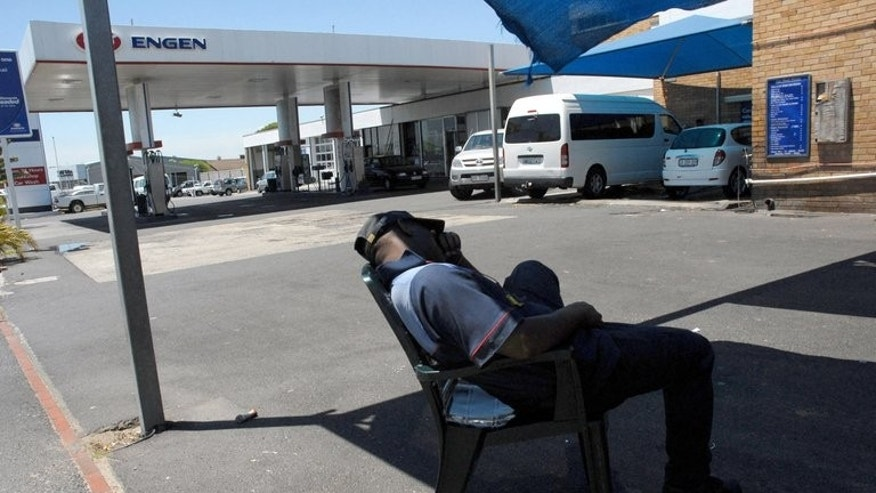 A petrol attendant takes a break in Cape Town. Tens of thousands of South African petrol attendants and car repair workers will strike for higher wages and better conditions, their union said, as stoppages in other sectors wound down.