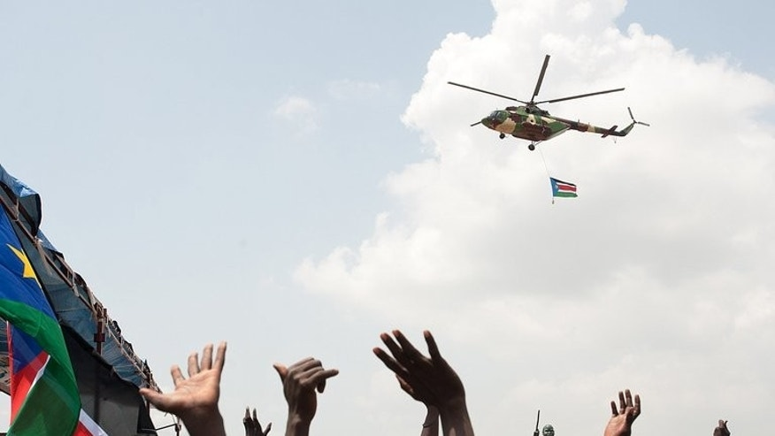 An SPLA helicopter flies the national flag over crowds on the first independence anniversary of South Sudan in Juba on July 9, 2012.