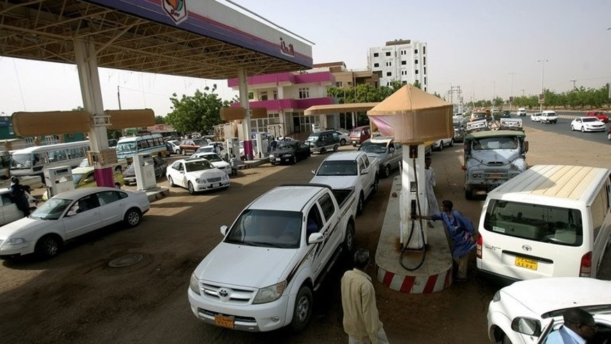 Sudanese queue in a petrol station to fuel their vehicles in Khartoum on June 21, 2012.