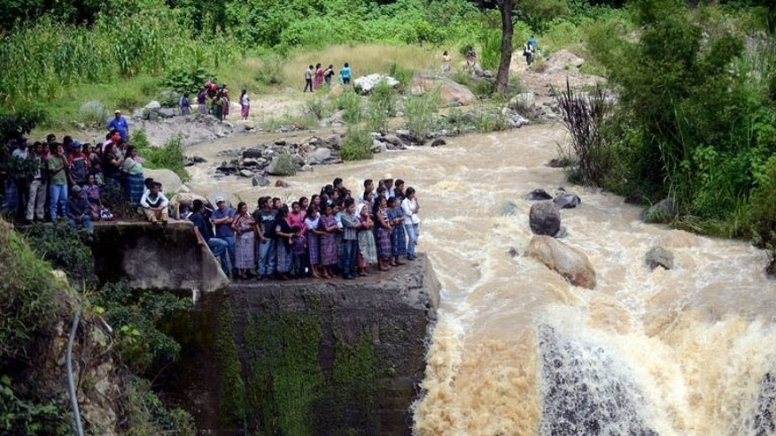 People look at the site of a bus accident on September 9, 2013 in the municipality of San Martin Jilotepeque. President Otto Perez declared three days of official mourning for the tragedy, one of the deadliest in the Central American nation in years.