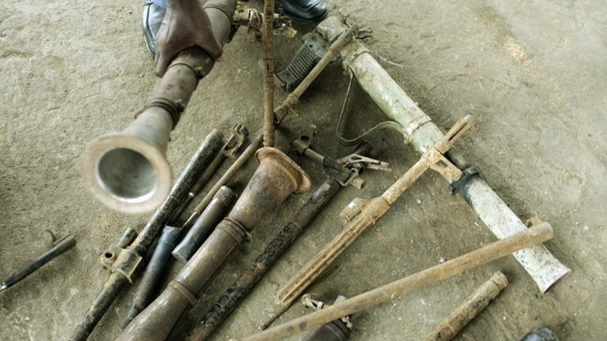 A Liberian holds an old bazooka as he works for a project to make tools out of weapons in Monrovia, October 7, 2007. Weapons which were once the cause of untold misery in a nation scarred by civil wars are now being transformed into symbols of hope for Liberians.