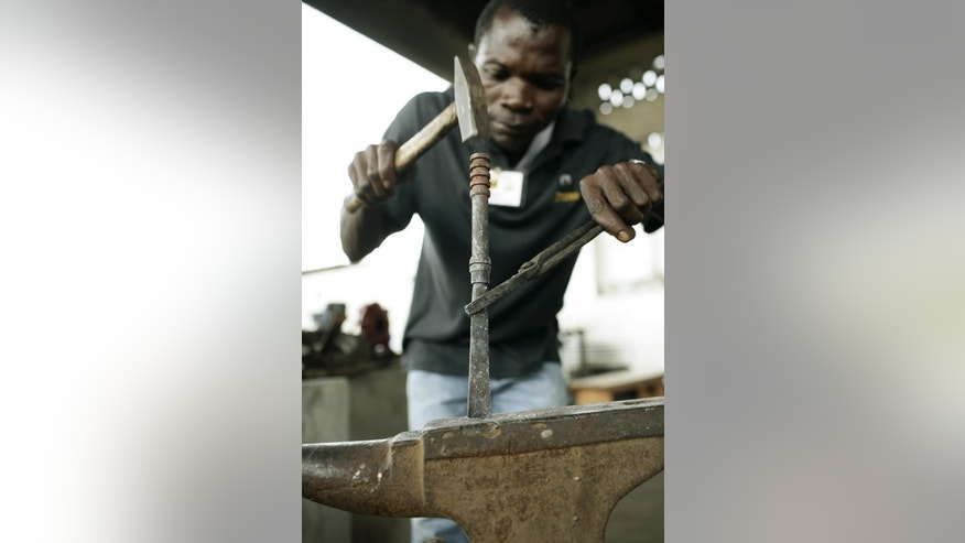 A Liberian forges a chisel from a gun barrel as part of a projet to make tools out of weapons in Monrovia, October 7, 2007. Weapons which were once the cause of untold misery in a nation scarred by civil wars are now being transformed into symbols of hope for Liberians.