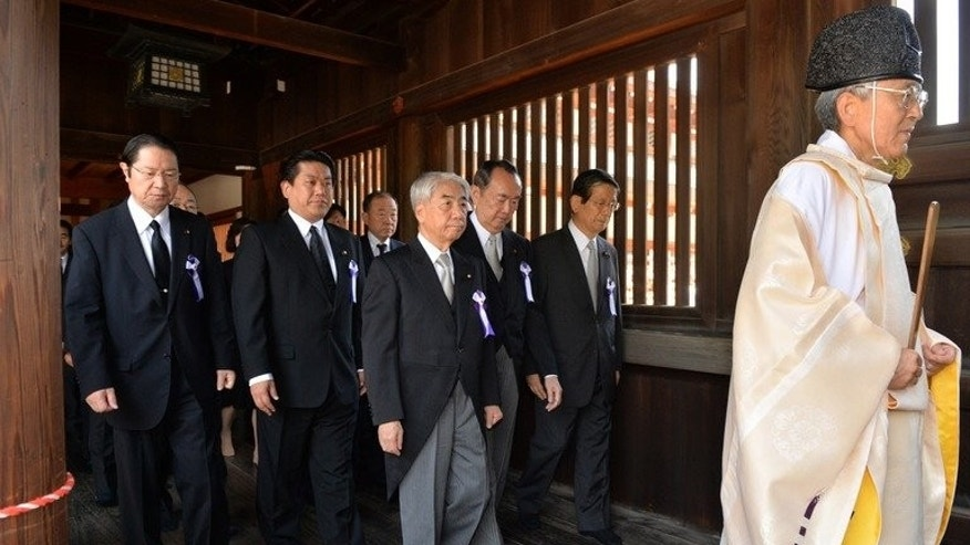 Japanese lawmakers follow a Shinto priest during a visit to the controversial Yasukuni shrine on August 15, 2013. CHiese stat-run media offered Tokyo heavily-qualified congratulations over their successful Tokyo Olympics bid.