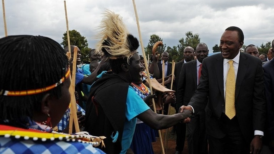 Kenya's President, Uhuru Kenyatta (R), and his deputy, William Ruto (2nd R) are welcomed by a dancing troupe on September 7, 2013 at Eldoret, in the North-Rift.