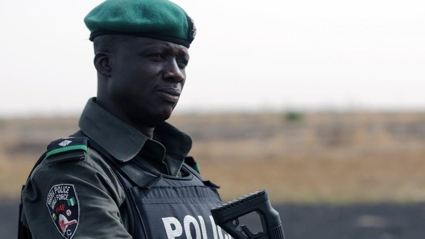 A Nigerian policeman patrols with Nigerian soldiers in the north of Borno state on June 5, 2013 near Maiduguri.