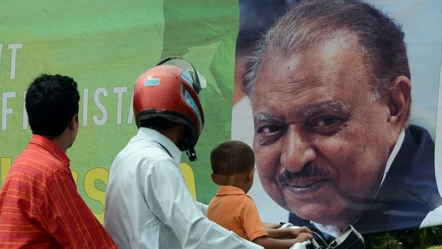 Commuters pictured in front of a roadside banner welcoming and congratulating incoming Pakistani President Mamnoon Hussain in Islamabad on September 9, 2013. He took office on Monday, presiding over a government battling to overcome a Taliban insurgency, resolve an energy crisis and repair the economy.