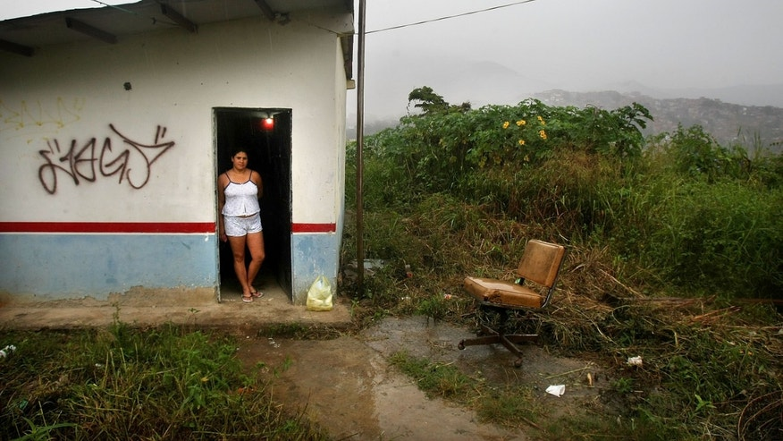 Carolina Olivera stands in her front door in the poor barrio of Petare in Caracas, Venezuela.