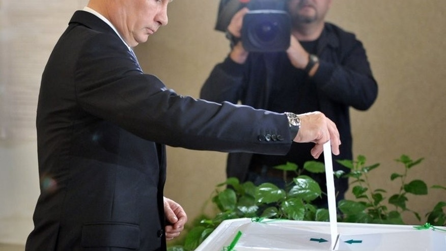Russia's President Vladimir Putin votes at a polling station during a mayoral election in Moscow, on September 8, 2013.