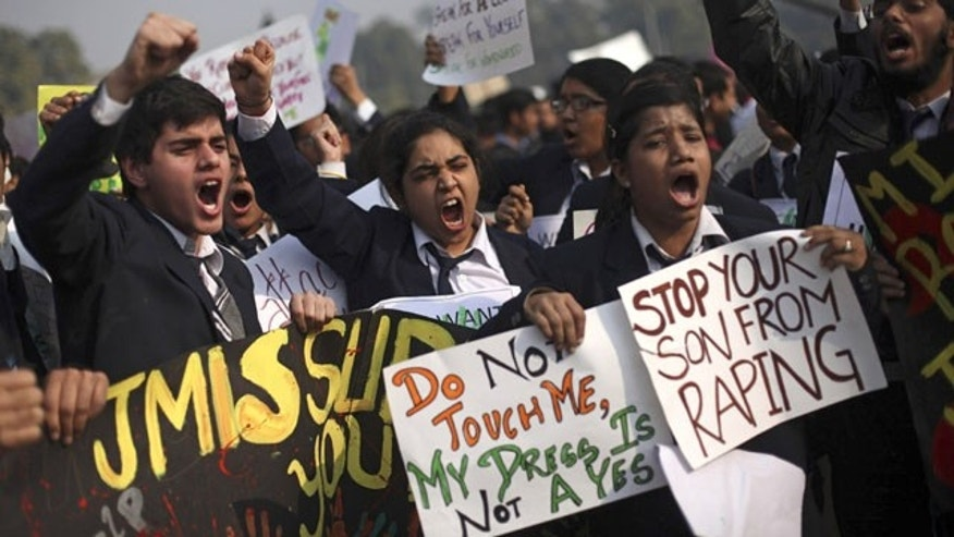 In this Dec. 22, 2012 file photo, Indian schoolchildren hold placards and shout slogans during a protest against the Dec. 16 gang rape and beating of a young woman on a city bus in New Delhi, India. (AP Photo)