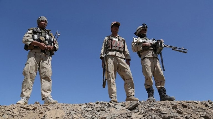 Afghan security forces stand guard in Zana Khan district in Ghazni province on August 27, 2013. A roadside bomb ripped through a passenger bus, killing seven civilians and wounding more than a dozen others in southern Afghanistan on Tuesday, officials said.