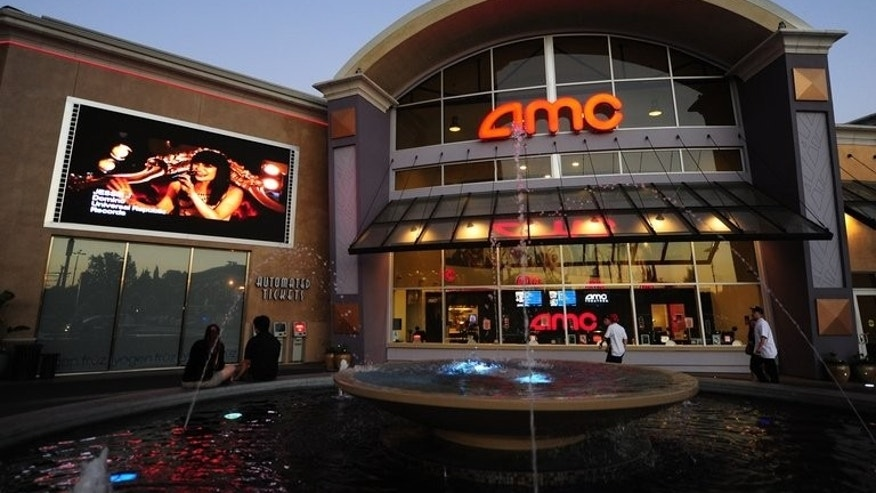 A couple watch a big screen outside an AMC cinema in Los Angeles on May 22, 2012. Chinese owner of AMC Entertainment, Wang Jianlin, has been named by Forbes magazine as China's richest man, with an estimated $14 billion.