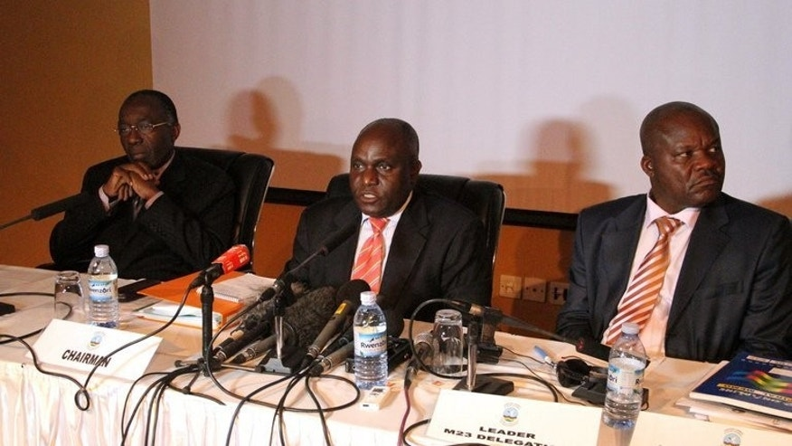Democratic Republic of Congo Foreign Minister Raymond Tshibanda (left), Ugandan Defense Minister Crispus Kiyonga (centre) and M23 leader Roger Lumbala hold a press conference in Kampala, on February 6, 2013. The government of the Democratic Republic of Congo and M23 rebels have restarted peace talks following an ultimatum set by regional leaders, according to the chief mediator.