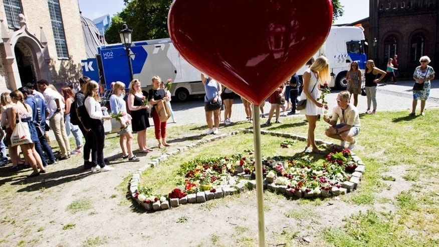 People lay flowers outside Oslo Cathedral, after a memorial service for the second anniversary of the massacre by Anders Breivik on July 22, 2013. Four young Norwegian Labour Party members who survived rightwing extremist Anders Behring Breivik's bloody rampage two years ago have been elected to parliament, the party said Tuesday.